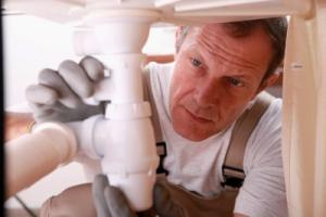 a South Gate plumber installs a new PVC drain system to a kitchen sink